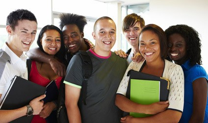 A group of adolescents smiling with backpacks and folders