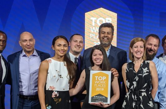 group of men and women business casual posing with top workplaces award