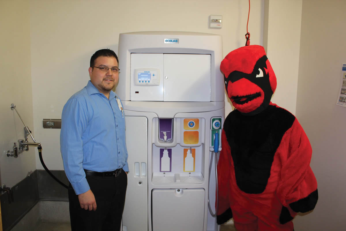 Julian Gonzalez, ARAMARK director of custodial services, and Red the Cardinal, pose in the nursing building with one of two new Electrically Activated Water (EAW) cleaning system units on campus.