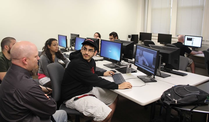 Adam Watkins (left), associate professor of Computer Graphic Arts, assists a team of advanced students with a game design during class.