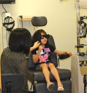 An RSO student administers an eye exam to an NISD student.
