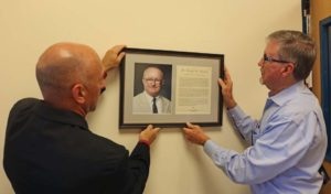 (L-R) Scott LeBlanc, director of sports and wellness, and Carleton hang the official plaque honoring Henrich at the center.