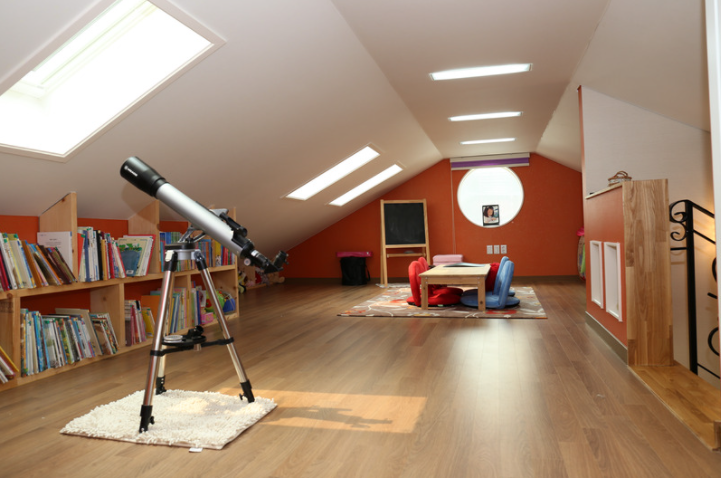 A child's dream attic space set up with books, a telescope, and craft area
