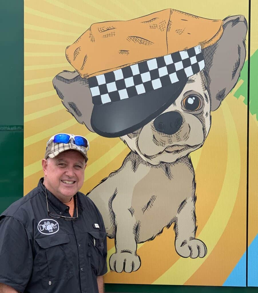 Ron Valez owner of duber dogs pet taxi service poses next to his pet transport bus