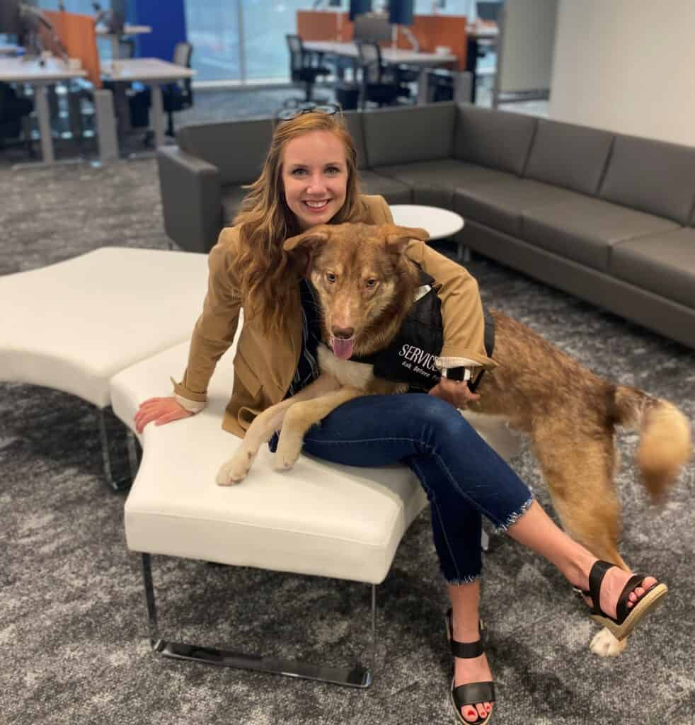 Kaydin Downey and her Service Dog and medical alert dog Hamilton provide consulting services at offices. Image shows Kaydin in an office, seated on a white leather sofa. Hamilton is applying pressure on her lap with his paws and torso.
