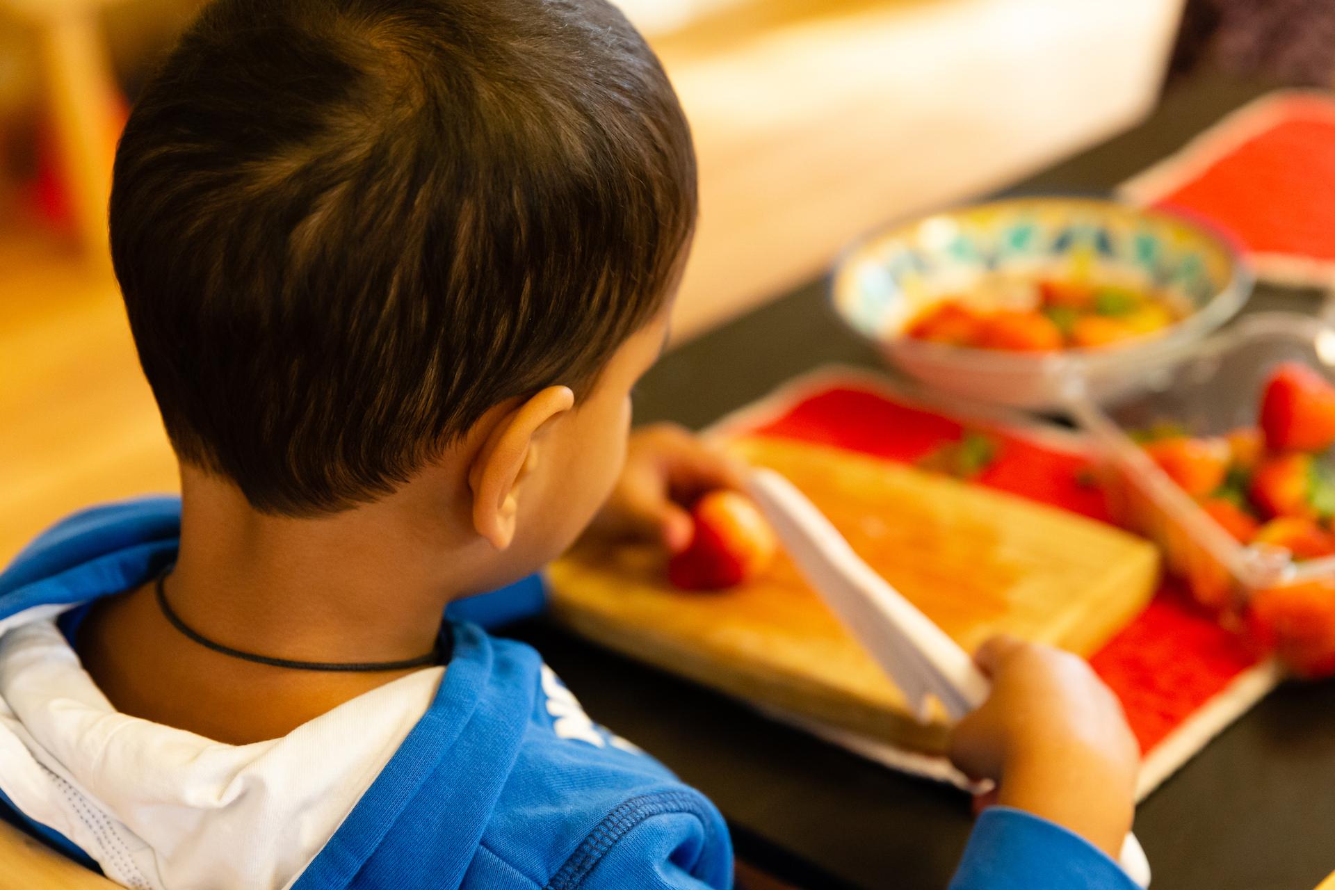 La Jolla Montessori School Boy Cutting Strawberries