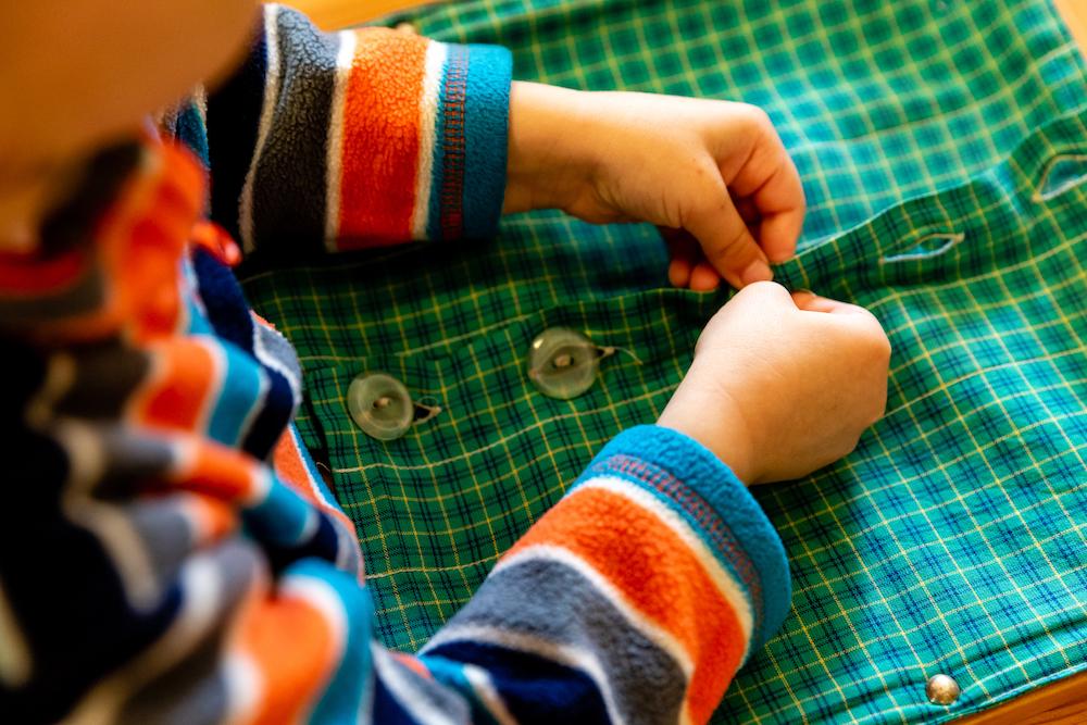 Child buttoning green shirt