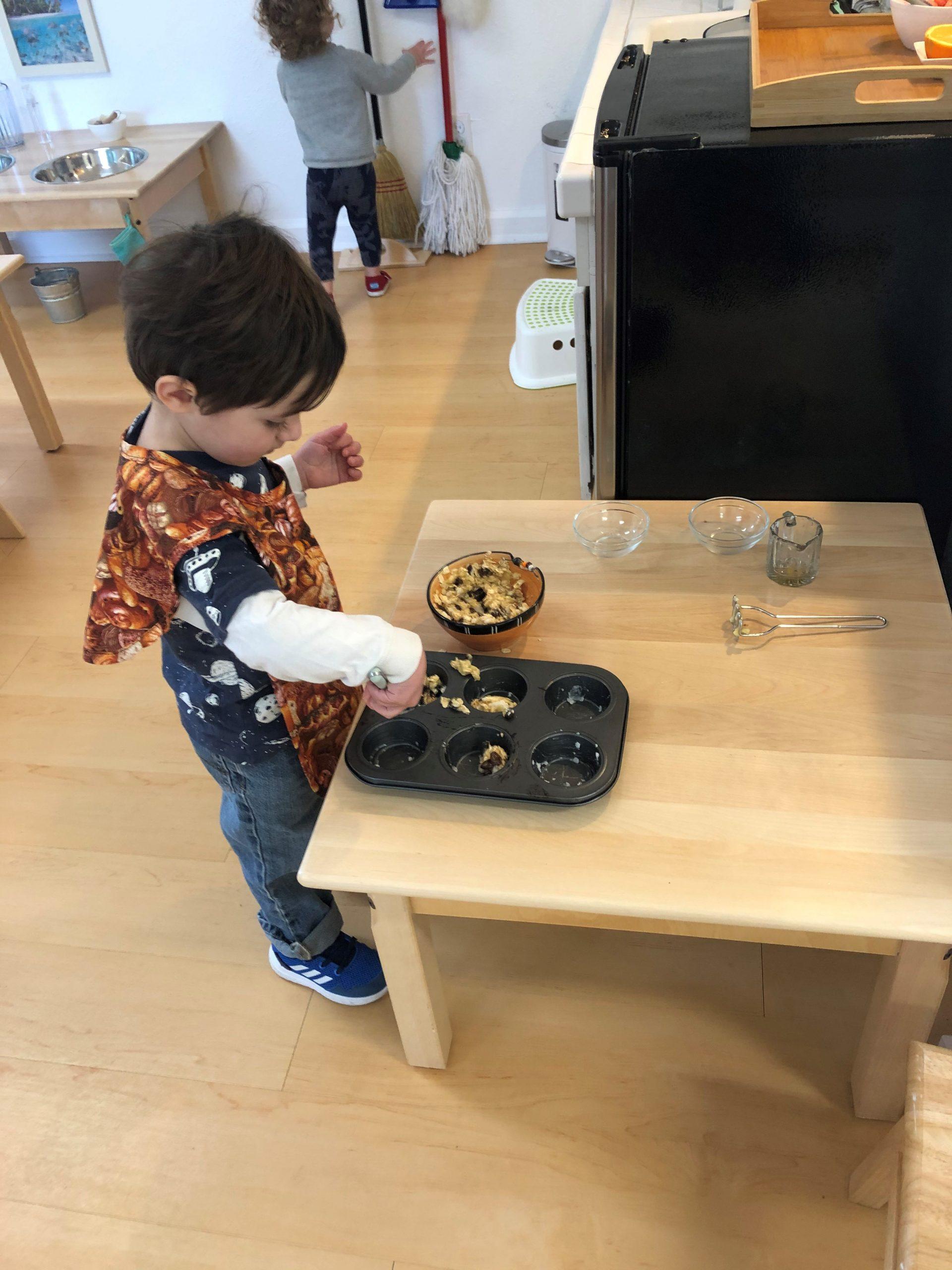 Toddler baking muffins