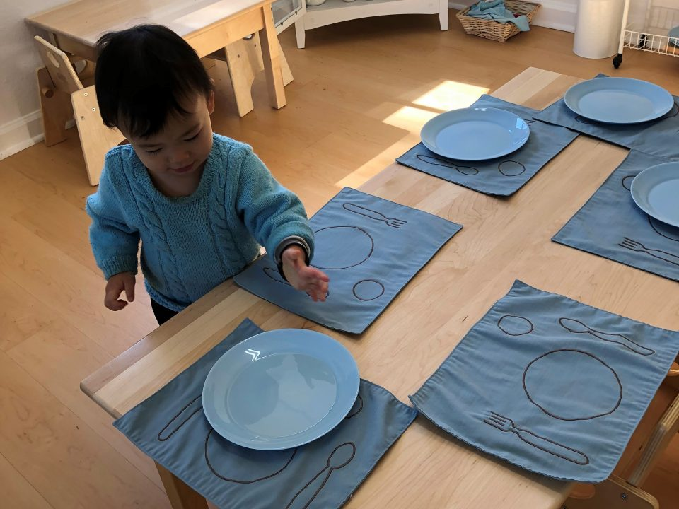 Toddler setting the table for lunch