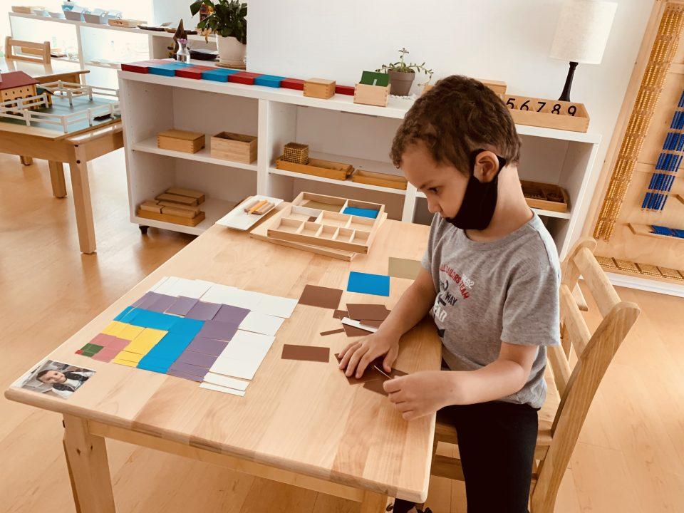 Boy using emotional intelligence while working on montessori math pricipals