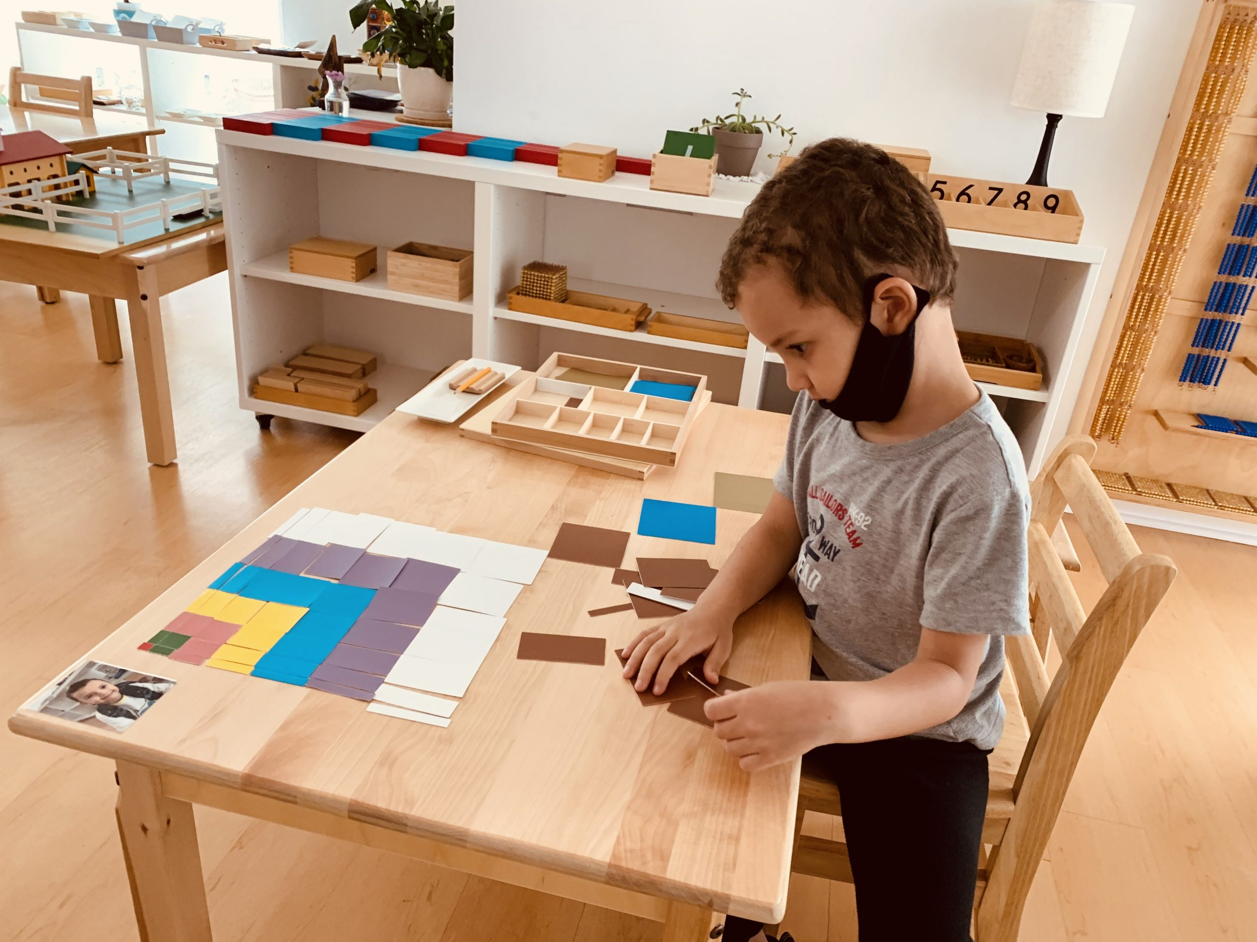 Boy using emotional intelligence while working on montessori math pricipals