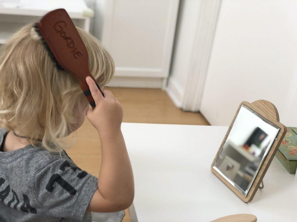 Toddler independently brushing his hair at La Jolla Montessori School
