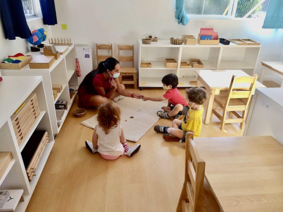 Montessori classroom with teacher guiding primary students