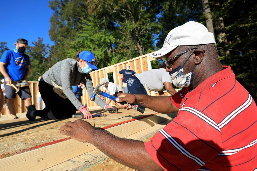 Wardell Newby drives nails into a wall that will one day make up his house at a Habitat for Humanity build