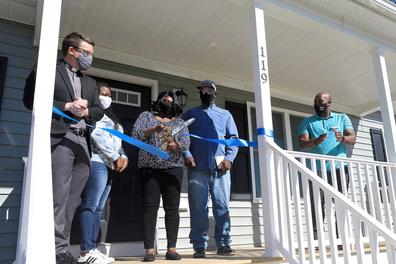 Jennifer Newby with husband Wardell cuts the ribbon on her new Habitat for Humanity home