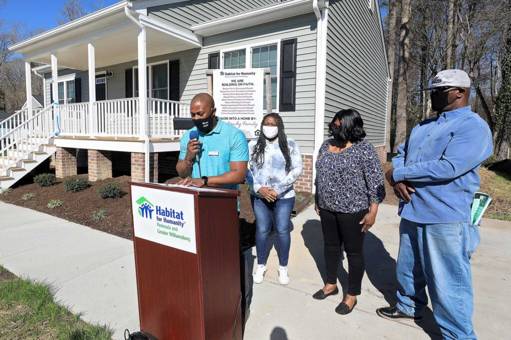 Habitat for Humanity's Chris Wayne leads the dedication ceremony for the Newby family's new home