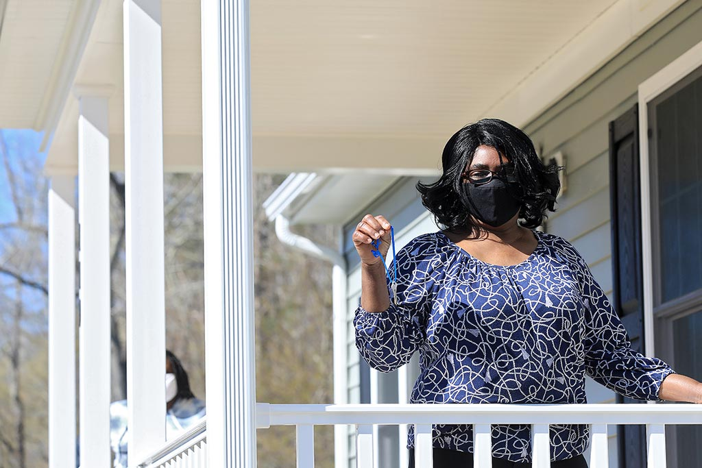Woman stands on the porch of her new Habitat for Humanity home in Williamsburg Tuesday March 30, 2021.