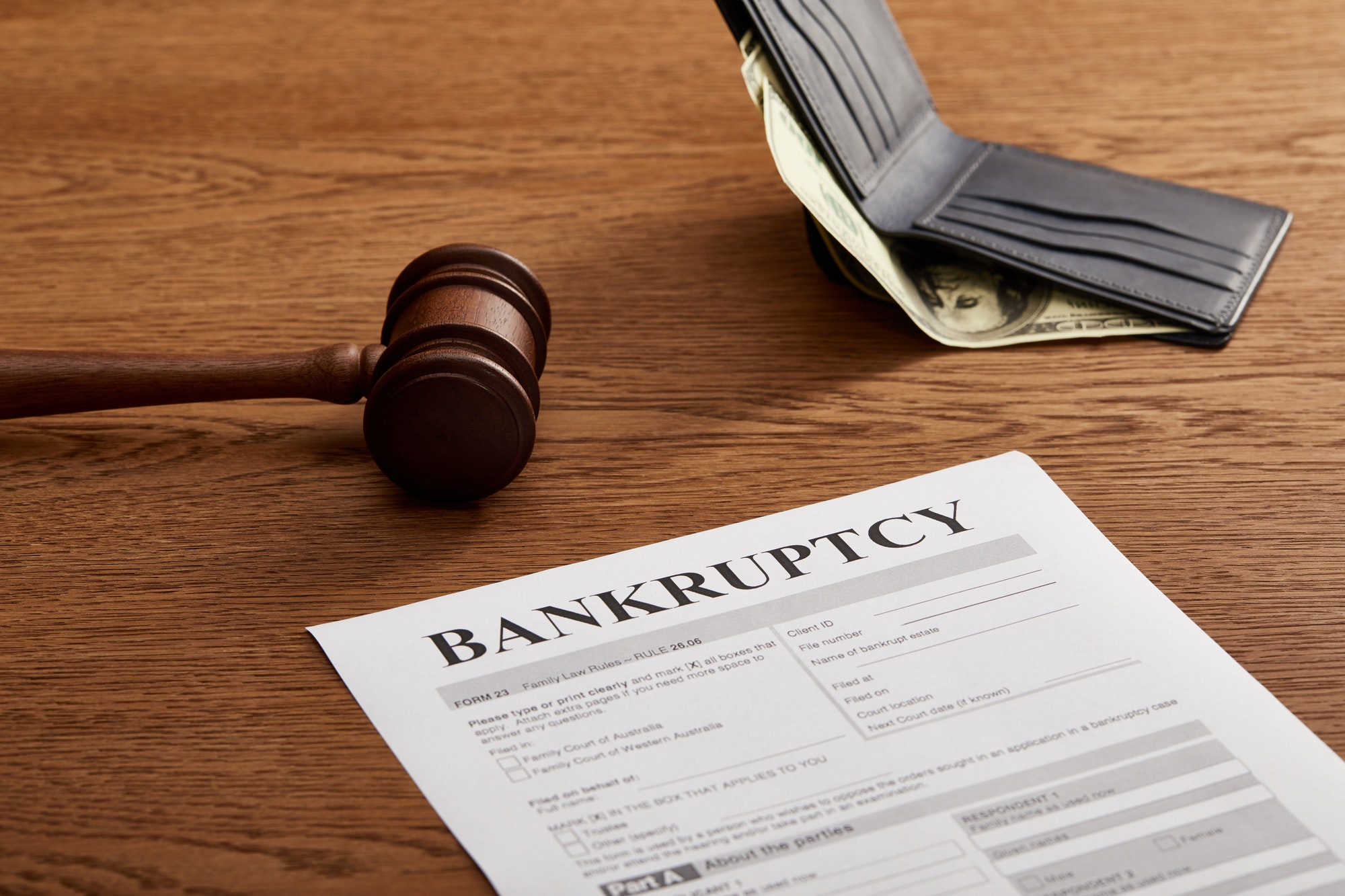 bankruptcy form with wooden gavel, dollar banknote and wallet on brown wooden table
