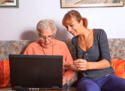 caregiver and senior woman using laptop