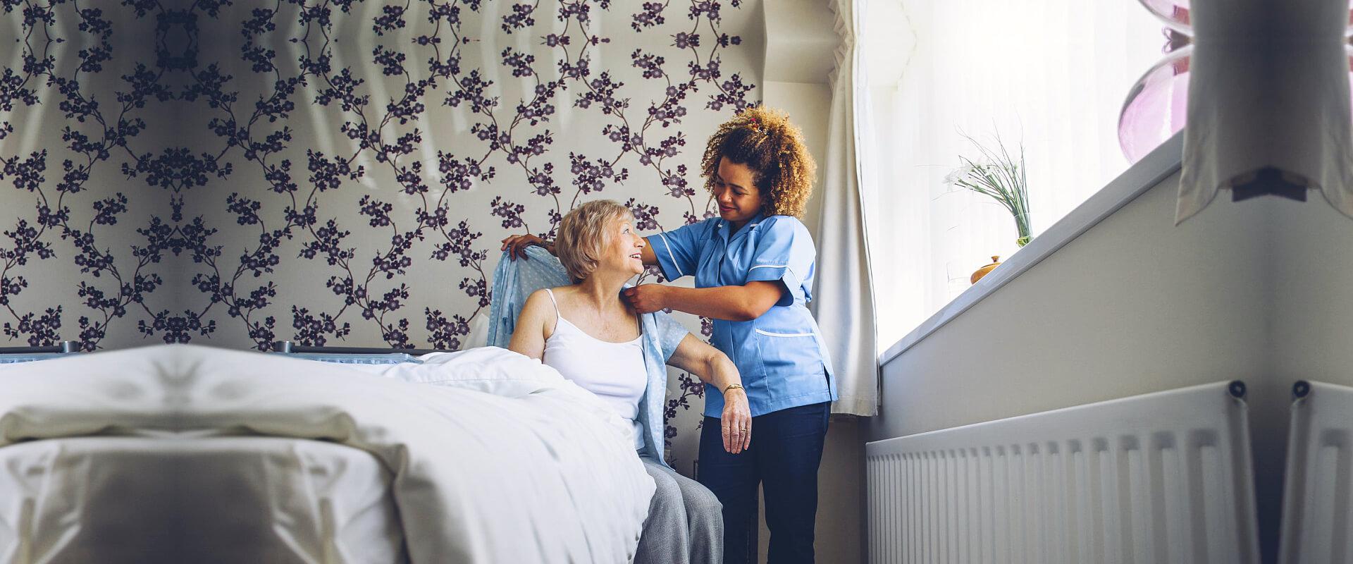 caregiver assisting senior woman get dressed