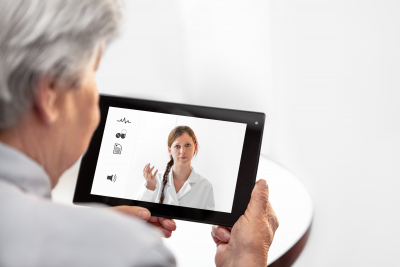nurse assisting senior woman through tablet device