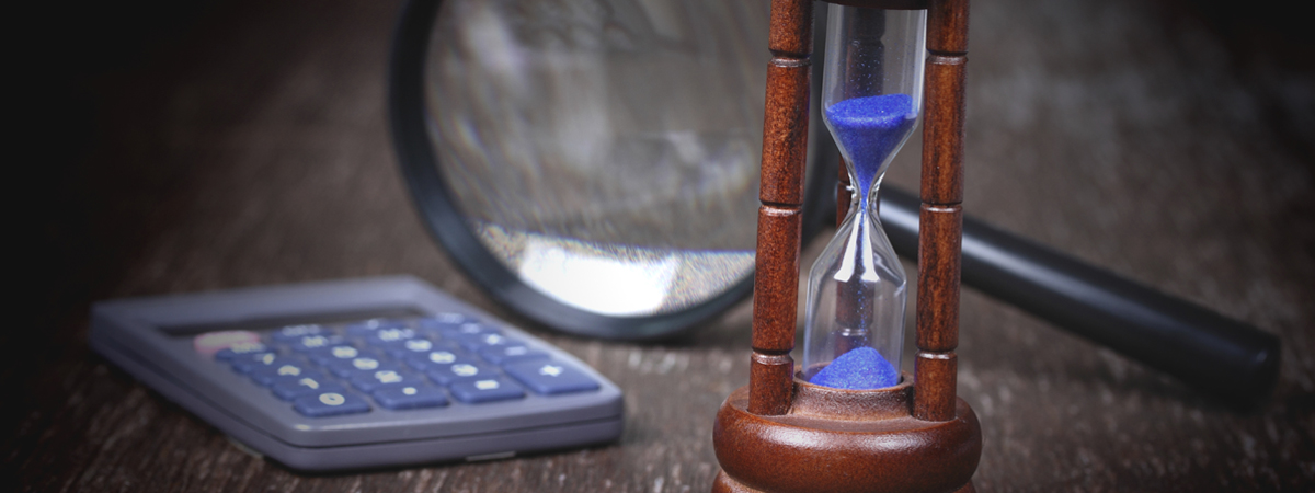 Group of objects on wood table. Hourglass, magnifying glass, calculator  , Studio shot.