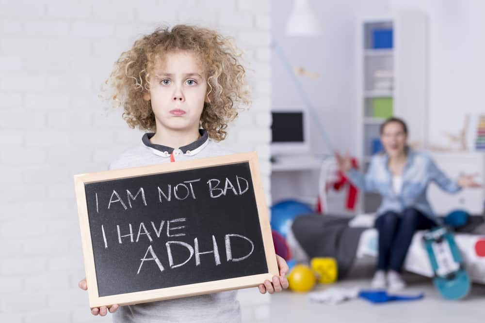 Sad,Adhd,Boy,Holding,Small,Board,,Shouting,Mother,In,Background