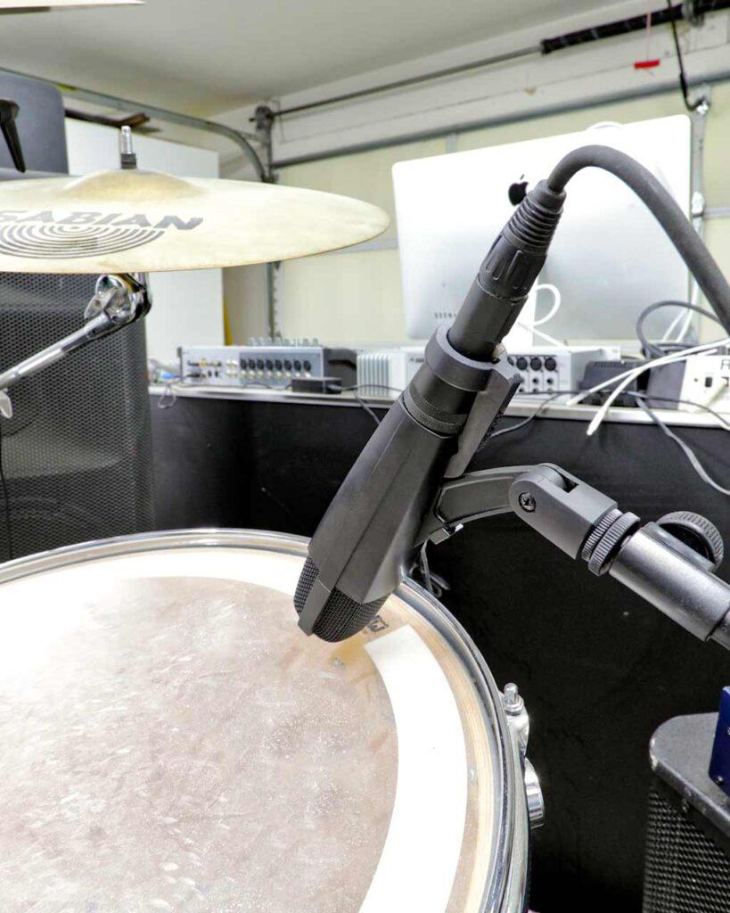 A Sennheiser MD421 with a black MicLock clip arm on a drum