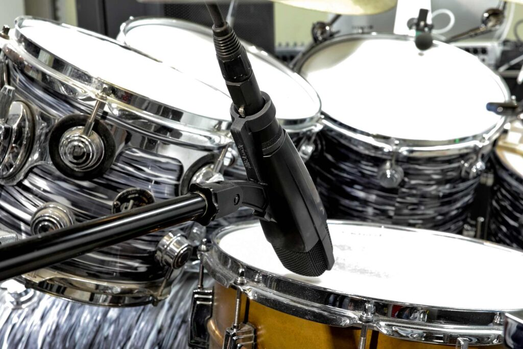 A Sennheiser MD421 with a black MicLock clip arm over a drum set.