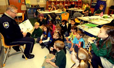 Sheriff's Dep, Eric Eilers reads a book to 4th-graders in the classroom of teacher Tara Sibal at Joseph Davies Elementary School on Nov. 14.