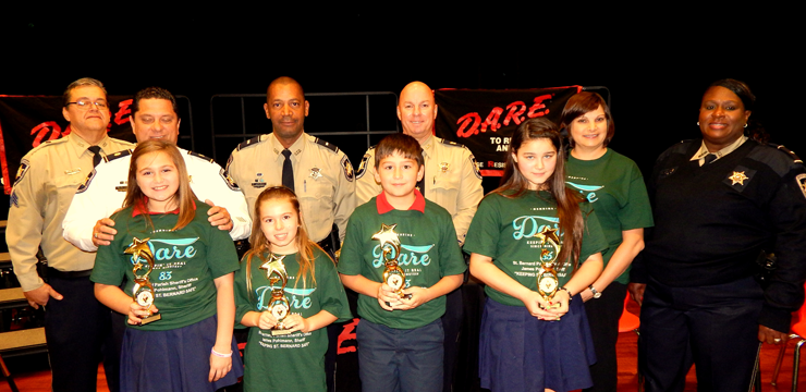 At. Gauthier Elementary, D.A.R.E. essay winners, from left, were Leah Thomassie, Cameryn Johnson, Glenn Mankin and Alyssa Laurente. Behind them are D.A.R.E. instructor Sgt. Darrin Miller, Maj. Chad Clark, Lt. Richard Jackson, Capt. Ronnie Martin, Principal Lisa Young and Lt. Lisa Jackson, head of the D.A.R.E. program.