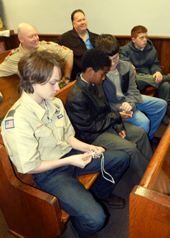 Boy Scouts look at items of contraband seized from prisoners who had made them.