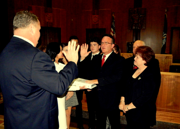 Perry Nicosia is sworn in as St. Bernard Parish District Attorney Sunday night by Clerk of Court Randy Nunez as Nicosia's wife, Nicole, his parents and others surround him in the large courtroom in the Parish Courthouse.