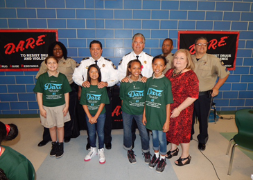 Essay winners at Arabi Elementary were, in front, April Liebert, Chobie Chan, Diamond Jones and Ramiyah Guerra. At right is Principal Carla Carollo. In back from left, are: Lt. Lisa Jackson, Maj. Chad Clark. Sheriff James Pohlmann, Lt. Richard Jackson and Sgt. Darrin Miller.