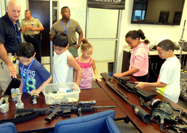 Junior Deputy Academy participants examine weapons and projectiles laid out in:the Sheriff's Office Training Center. Behind them, from left, are officers Lt. Raymond Theriot, Lt. Mike Ingargiola and Det. Sgt. Donald Johnson, a SWAT team member.