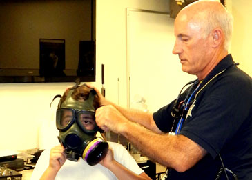 Lt. Raymond Theriot helps place a gas mask on a participant.