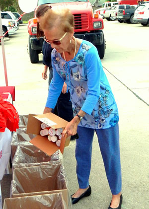 A woman empties prescription pill bottles she is surrendering into a container at the Sheriff's Office drug Take-Back Day in September 2014.