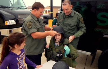 Maj. Robert McNab and Lt. Richard Mendel put a SWAT helmet and jacket on a girl.
