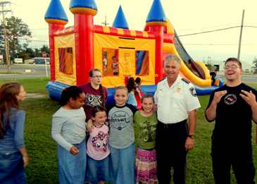 Sheriff Pohlmann with a group of young people outside a bounce tent on church grounds.