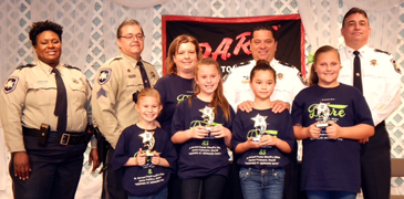 D.A.R.E. essay winners at Our Lady of Prompt Succor were, from left in front,, Ella Lafrance, Halli Diecidue, Shania Raimer and Kathryn Kamlade. In back are Lt. Lisa Jackson, Sgt. Darrin Miller, School D.A.R.E. moderator Rachel Vogt, Maj. Chad Clark and Col. John Doran.