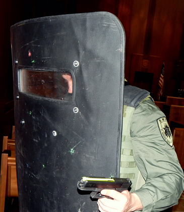 A S.W.A.T. team member holds a shield to lead a practice  advance.at the Courthouse.