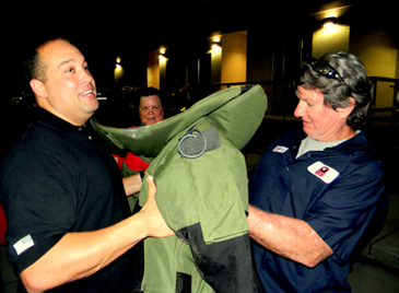 Lt. Stephen Ingargiola, left, hands a 90-pound bomb squad jacket to a participant in a Sheriff's Office Citizens Police Academy class in 2012.