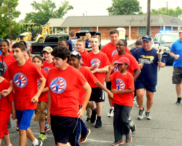 Some of the Special Olympics competitors on West St. Bernard Highway at the start of the Torch Run. They ran only a short distance before boarding a bus to Hammond for the state Summer Games.