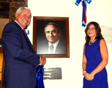 Attorney Anthony Ferndnadez Jr., and Rebecca Schoen, grand-daughter of the late Jack Rowley, unveil a photo and plaque of Rowley in the lobby of the St. Bernard Courthouse on June 20, as part of a ceremony dedicating the building in honor of the former long-time District Attorney and Sheriff. Fernandez organized the event.