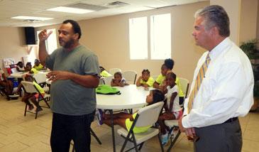 Pastor Henry Ballard Jr. and Sheriff James Pohlmann talk to kids at Christian Fellowship summer camp.