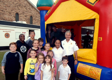 Sheriff James Pohlmann  with children outside a bounce house at First Pentecostal Church in Chalmette during a party for the celebration of National Night Out Against Crime on Oct. 18