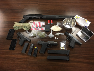 The heroin, MDMA, pills, four guns, cash and drug paraphernalia seized in the arrests of two men.