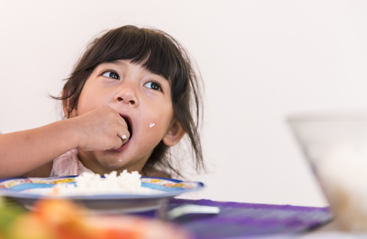 kid eating rice with her hands