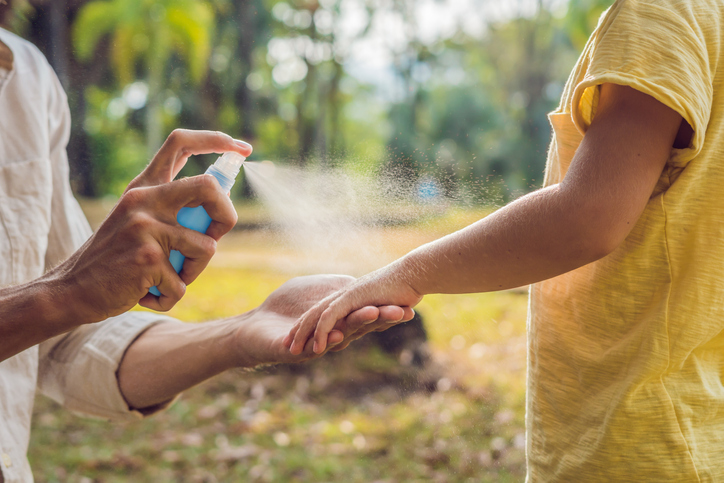 person using mosquito spray on kid