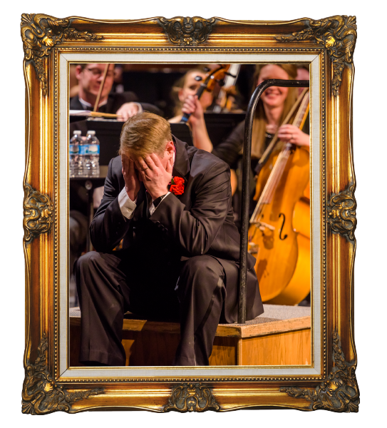 Conductor sitting in front of orchestra in gold frame